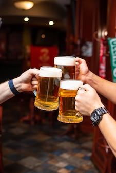 Ausschenkendes bier steht an der theke. großes handwerkliches bier vom fass im café oder pub-menü. anstoßen mit freunden an der bar