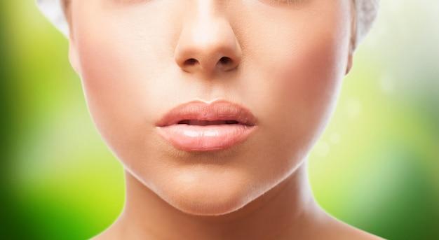 Ausschnitt der weiblichen lippen auf grünem hintergrund.