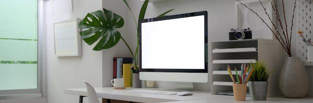 Ausschnitt des minimalen büroraums mit computer mit leerem bildschirm, büromaterial und dekorationen