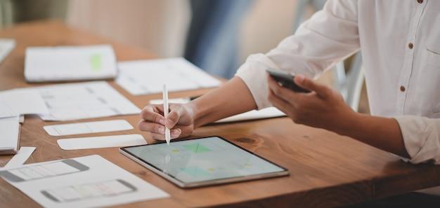 Ausschnitt einer jungen webentwicklerin, die an ihrem projekt arbeitet, während sie ein digitales tablet verwendet