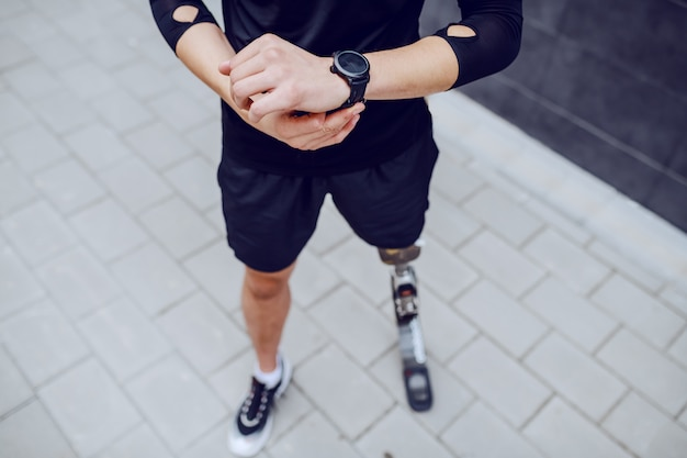 Ausschnittbild des kaukasischen sportlers mit künstlichem bein, das armbanduhr betrachtet.