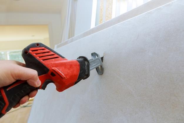 Ausschnittgipsplatte der trockenmauerhand mit schmutziger säge des schmutzes
