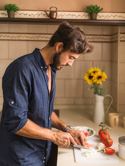 Ausschnittscheiben des jungen mannes des rettichs im küchentheke
