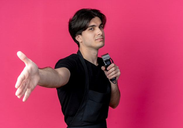 Aussehender junger gutaussehender männlicher friseur in uniform, der haarschneidemaschinen hält und die hand ausstreckt