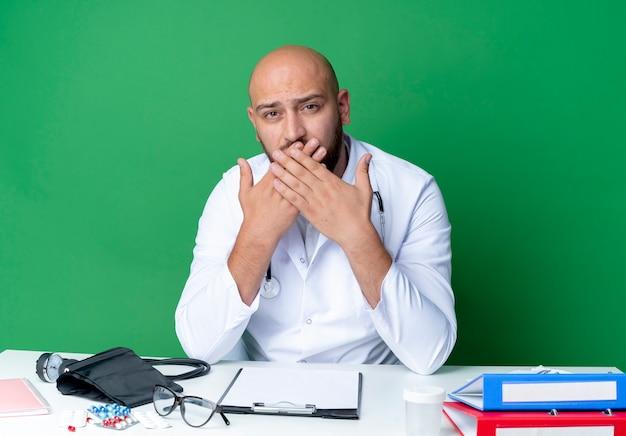 Aussehender junger männlicher arzt, der medizinisches gewand und stethoskop trägt, der am schreibtisch sitzt