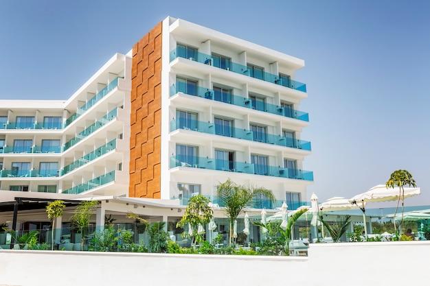 Außenansicht des hotels im resort mit swimmingpool und liegestühlen.