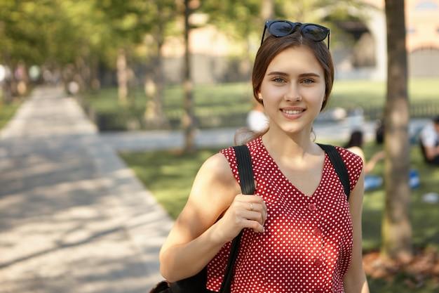 Außenansicht des schönen niedlichen studentenmädchens, das gepunktetes oberteil und schatten auf ihrem kopf trägt rucksack trägt, im park nach der universität gehend. stilvolle frau, die geht. menschen- und lebensstilkonzept