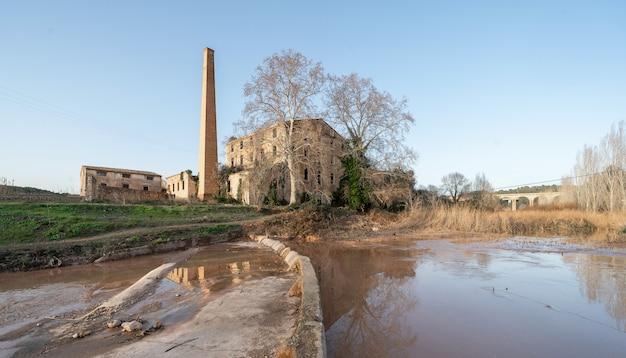 Außenansicht einer großen alten verlassenen fabrik neben dem fluss