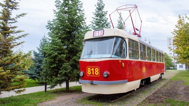 Außenansicht einer vintage rot-weißen straßenbahn auf der eisenbahn als exponat mit 818 nummer darauf, grün herum, chisinau, moldawien