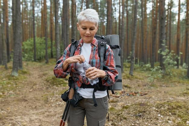 Außenaufnahme der aktiven kaukasischen frau mittleren alters, die rucksack öffnet, die flasche wasser öffnet, sich während des langen anstrengenden trekkings im nationalpark erfrischend, gegen kiefern stehend