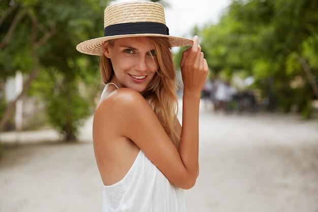 Außenaufnahme der angenehm aussehenden frau mit gebräunter gesunder haut, gekleidet in weißes kleid und sommerhut, wirft im park mit zuversichtlich zufriedenem ausdruck auf