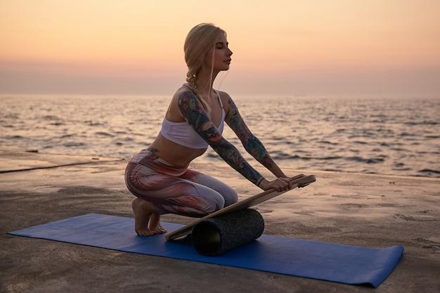 Außenaufnahme der blonden sportlichen frau mit körper in guter körperlicher verfassung, die über meerblick aufwirft, sport am frühen morgen mit matte und ausgleichsbrett macht, sportliches oberteil und leggins tragend