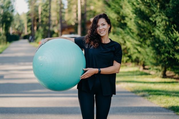 Außenaufnahme der brünetten frau posiert mit großem fitball in sportkleidung hat training im freien