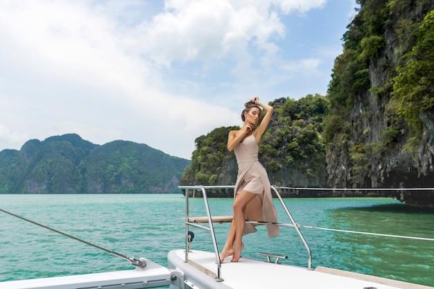 Außenaufnahme der entzückenden jungen frau im weißen beige kleid, das auf rand der yacht steht