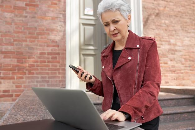 Außenaufnahme der ernsthaften grauhaarigen immobilienmaklerin in stilvoller kleidung, die außerhalb des backsteingebäudes vor offenem laptop steht, unter verwendung der drahtlosen internetverbindung