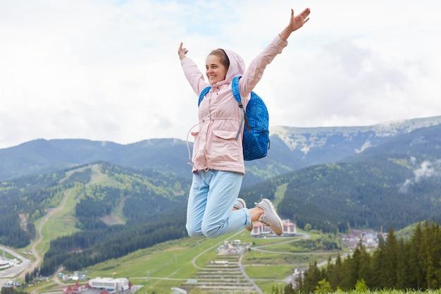 Außenaufnahme der frau, die hoch springt, hafenwandern an feiertagen. frau, die rosa jacke und blauen rucksack lokalisiert über berge trägt. konzept für reisen, abenteuer und aktive erholung.