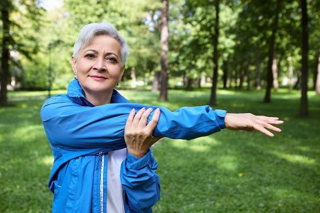 Außenaufnahme der gesunden sportlichen älteren frau mit dem kurzen grauen haar, das im park ausübt. ältere frau in der blauen sportjacke, die den armmuskel streckt und sich vor dem lauftraining aufwärmt