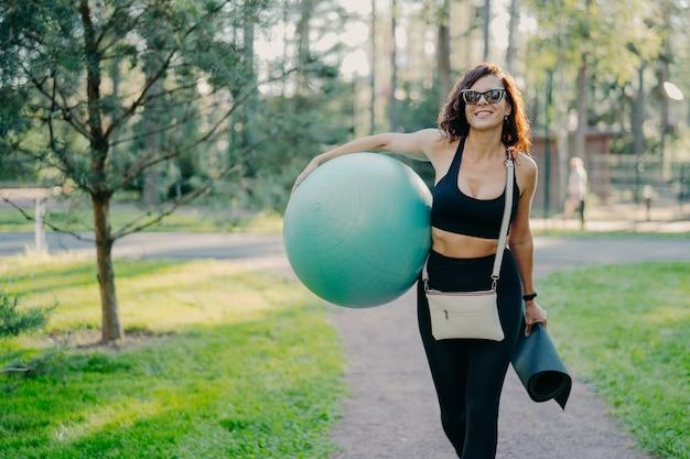 Außenaufnahme der glücklichen brünetten schlanken frau gekleidet in aktiver kleidung trendiger sonnenbrille