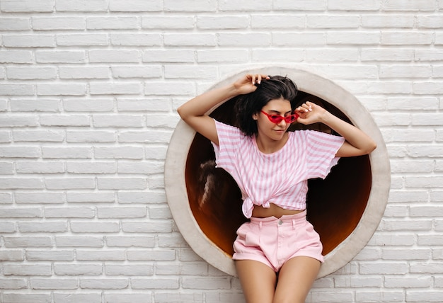 Außenaufnahme der inspirierten frau in der sonnenbrille. brünette frau in der sommerkleidung, die auf städtischem hintergrund aufwirft.