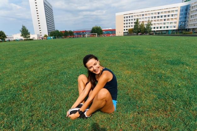 Außenaufnahme der jungen sportlerin, die auf rennstrecke läuft. profisportlerin während des lauftrainings.