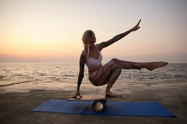 Außenaufnahme der jungen sportlich tätowierten frau mit lässiger frisur, die ihr gleichgewicht auf der sportausrüstung hält, während des sonnenaufgangs am meer aufwirft und sportliche kleidung trägt