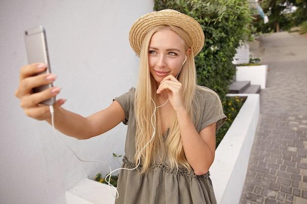 Außenaufnahme der niedlichen blonden frau im strohhut mit kopfhörern in den ohren, selbstporträt mit ihrem smartphone machend, zart und romantisch aussehend