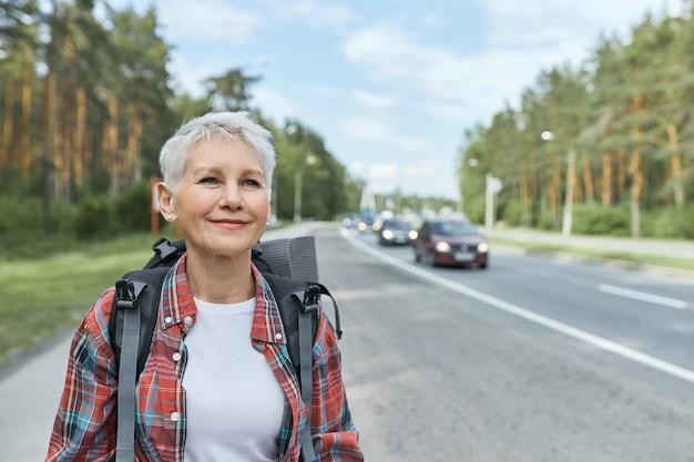 Außenaufnahme der schönen aktiven frau mittleren alters mit dem kurzen haarschnitt, der rucksack trägt, der entlang der hauptstraße beim trampen allein geht.