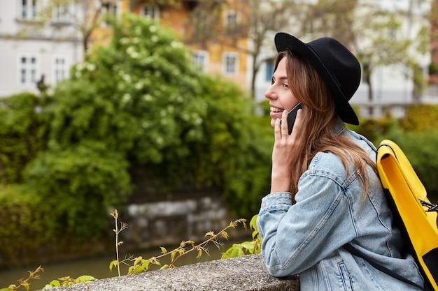 Außenaufnahme der schönen dame kommuniziert auf handy, bewundert wundervollen tag und sehenswürdigkeiten in ruhiger stadt