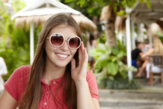 Außenaufnahme der schönen jungen frau, die ihre runde sonnenbrille des hipsters anpasst und mit glücklichem gesichtsausdruck schaut