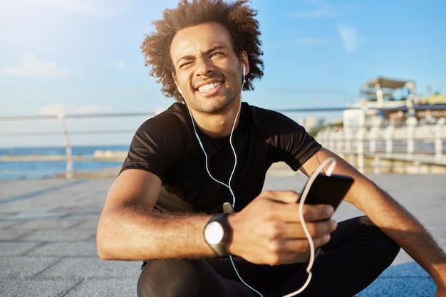Außenaufnahme des afroamerikanischen sportlers mit buschiger frisur, die wegen der sonne in der schwarzen sportkleidung blinzelt. dunkelhäutiger männlicher athlet, der mit gekreuzten beinen in seinem handhandy sitzt