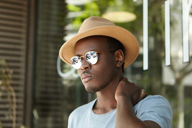 Außenaufnahme des attraktiven jungen männlichen afroamerikanertouristen, der sich vor sengenden strahlen der sommersonne im schatten des städtischen cafés versteckt, gekleidet in stilvolle kleidung, frustriert schaut und seinen hals reibt