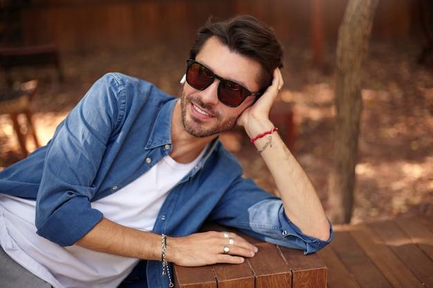 Außenaufnahme des attraktiven jungen mannes mit bart, der auf seinem kopf mit handfläche lehnt, über stadtgarten mit aufrichtigem lächeln aufwirft, lässige kleidung tragend