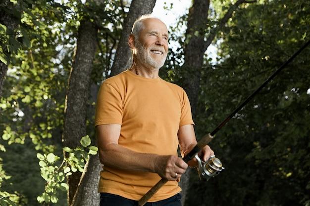 Außenaufnahme des attraktiven unrasierten älteren kaukasischen mannes, der die spinnrute hält, die in flusswasser geworfen wird, mit vorfreude lächelnd, darauf wartend, dass fisch gehakt wird, fackelsonne und grüne bäume herein