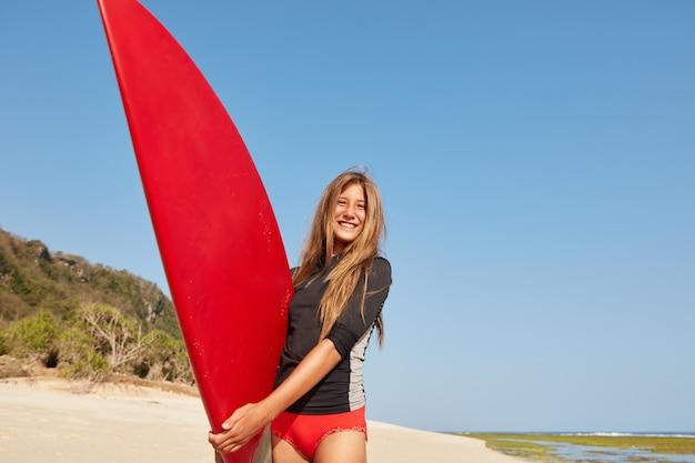 Außenaufnahme des glücklichen erstaunlichen aktiven mädchens hat sportlich perfekte figur, gesunden lebensstil, schlägt wellen mit surfbrett