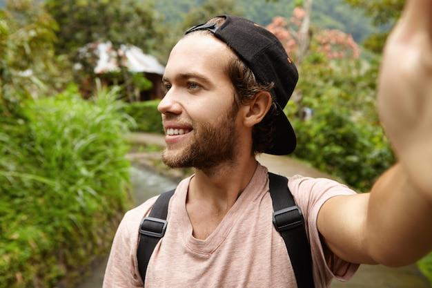 Außenaufnahme des glücklichen jungen hipsters, der rucksack und baseballmütze trägt selbstporträt nimmt, lächelt und wegschaut. hübscher reisender, der entlang landstraße geht