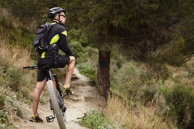 Außenaufnahme des jungen europäischen mannes, der fahrradkleidung, helm und brille trägt