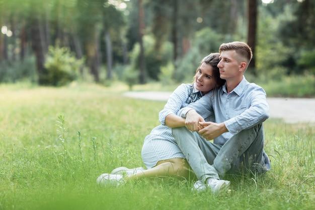 Außenaufnahme des jungen glücklichen paares in der liebe, die auf gras sitzt