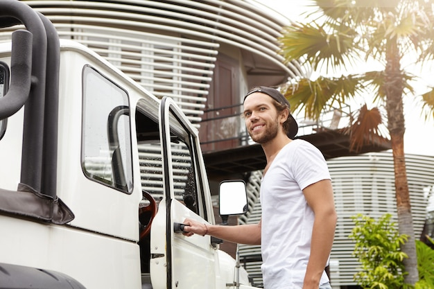 Außenaufnahme des jungen männlichen kaukasischen modells mit bart, der an seinem weißen crossover-nutzfahrzeug aufwirft, hand auf griff hält. stilvoller mann, der in sein auto steigt