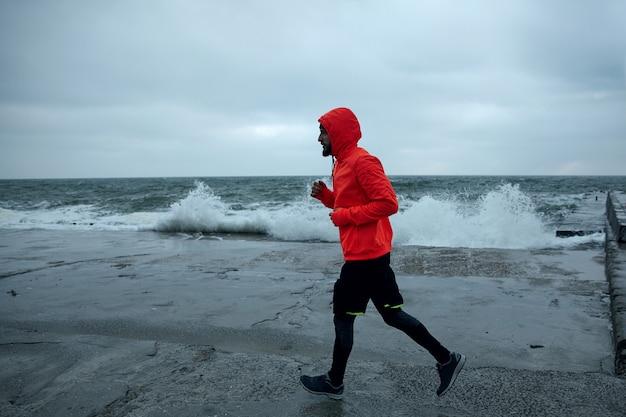 Außenaufnahme des jungen sportlers gekleidet in der warmen sportlichen kleidung, die auf grauem und stürmischem wetter über das meer läuft, konzentriert ist und hände auf brusthöhe hält