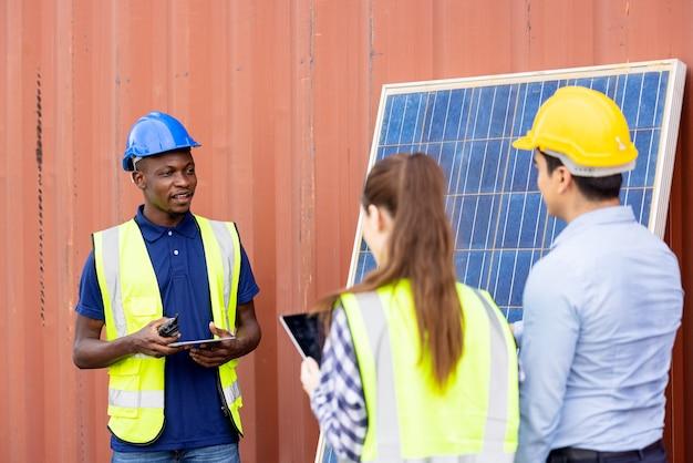 Außenaufnahme des schwarzafrikanischen ingenieurs inspizieren elektrisches solarpanel mit helm, schutzbrille und sicherheitsausrüstung,