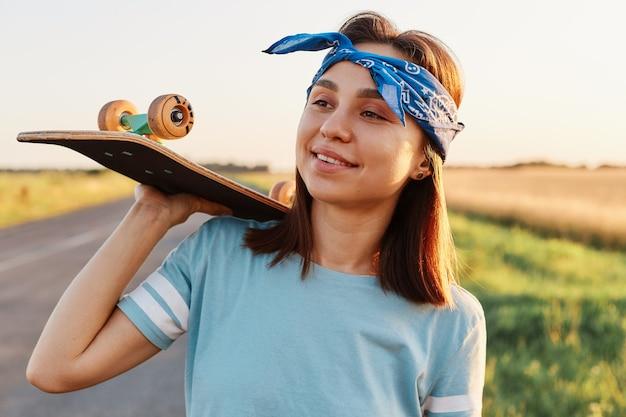 Außenaufnahme einer lächelnden brünetten frau, die lässiges t-shirt und haarband trägt, skateboard auf den schultern hält, mit einem lächeln wegschaut und glück ausdrückt.