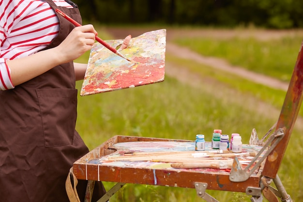 Außenaufnahme einer unbekannten frau um die natur, die eine braune schürze trägt, pinsel und palette hält, einen weiten pinselstrich macht, skizzen unter freiem himmel erstellt, röhren mit farben sind zu sehen.