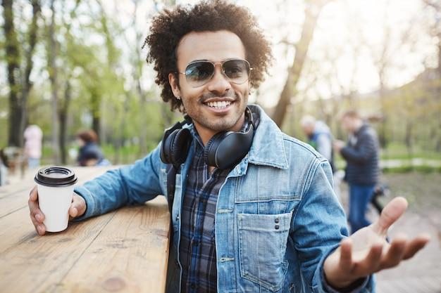 Außenaufnahme eines modischen dunkelhäutigen mannes mit afro-frisur, der eine trendige brille und kopfhörer über dem hals trägt, sich auf den tisch im park stützt und kaffee trinkt