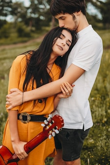 Außenaufnahme eines romantischen paares, das im freien umarmt. schöne junge brünette, die einen lehnenden gitarrenkopf mit geschlossenen augen auf der brust ihres freundes hält.