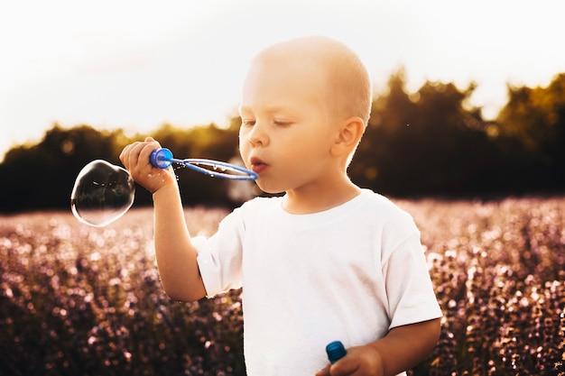 Außenaufnahme eines süßen kleinen kindes, das seifenballons gegen sonnenuntergang tut. schöner kleiner junge, der im blumenfeld spielt.