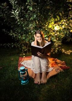 Außenaufnahme in der nacht einer frau, die ein buch im licht der gartenlaterne liest