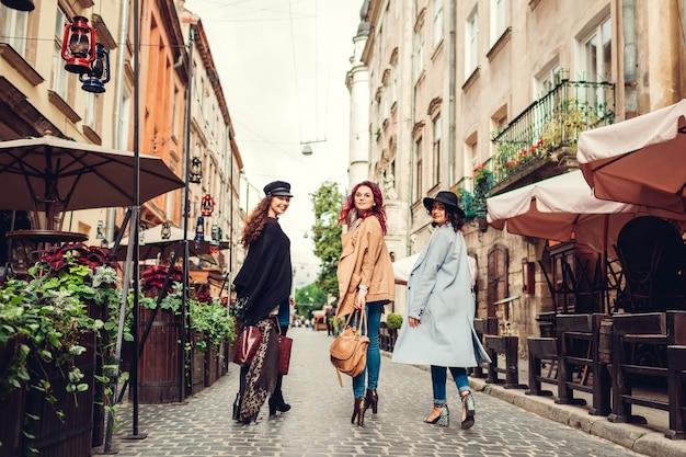 Außenaufnahme von drei jungen frauen, die auf der stadtstraße spazieren. mädchen drehen und betrachten die kamera. damen haben spaß