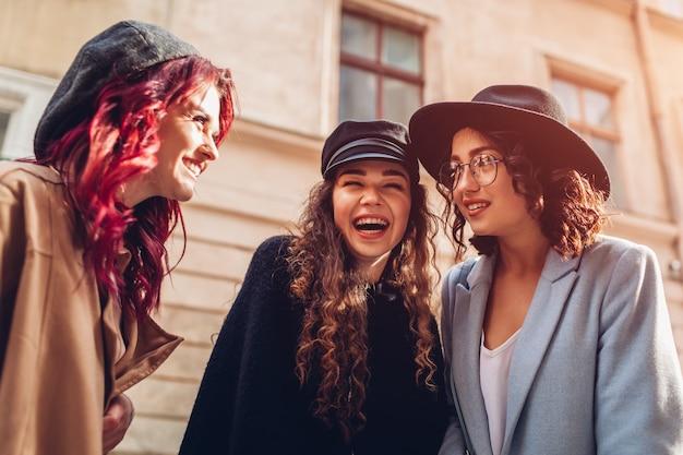 Außenaufnahme von drei stilvollen jungen frauen, die auf der stadtstraße sprechen. glückliche freundinnen, die sich unterhalten und spaß haben