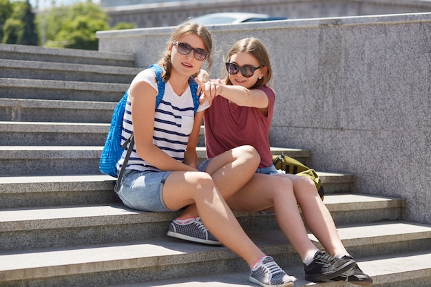 Außenaufnahme von teenagern verbringt freizeit zusammen, sitzt auf treppen, zeigt und schaut in die ferne, trägt sonnenbrillen, genießt die sommerzeit, trägt taschen, atmet frische luft. freundschafts- und freizeitkonzept