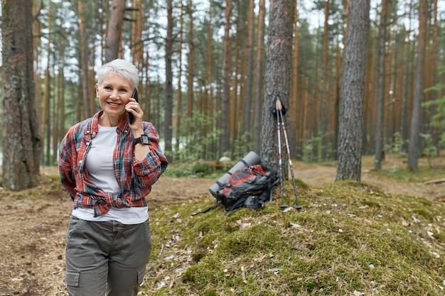 Außenbild der energetischen pensionierten frau in der aktivkleidung, die im wald geht, telefongespräch, lächeln, rucksack und schlafmatte unter baum im hintergrund hat. menschen, reisen und technologie